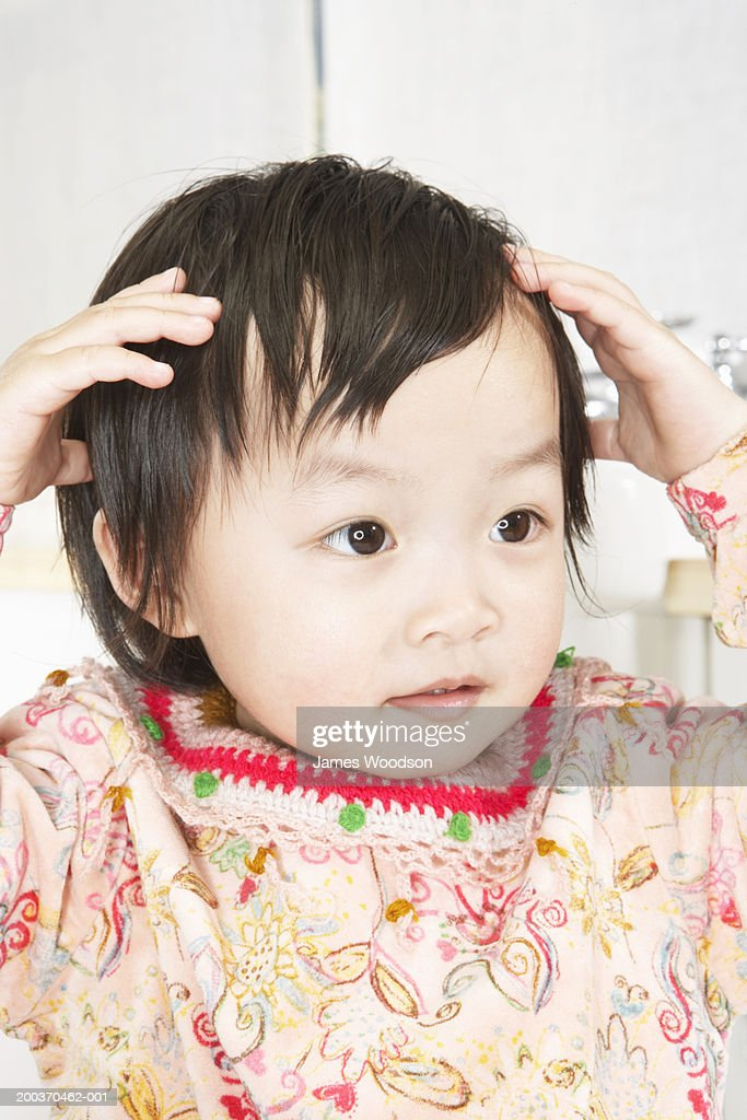 Toddler girl (21-24 months) touching head, close-up : Stock Photo