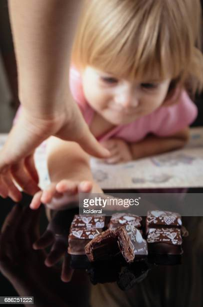 toddler girl tried to reach chocolate candies while mother stops her - streptococcus stock-fotos und bilder