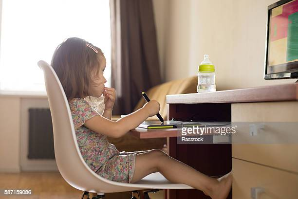 toddler girl using digital tablet for drawing and learning shapes