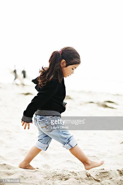 Toddler girl walking on beach