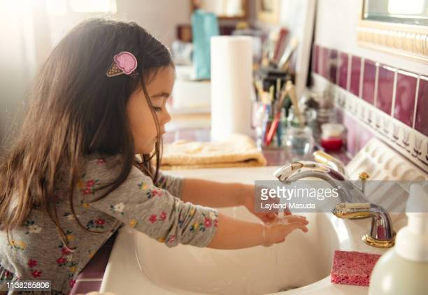 toddler girl washing her hands after painting - handwashing stock pictures, royalty-free photos & images