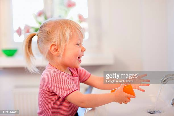 Toddler girl washing her hands