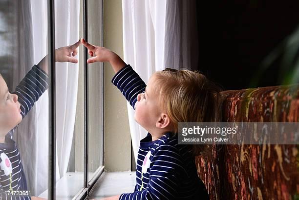 Toddler girl watching rain drops