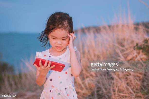 Toddler girl watching the photos she just shot
