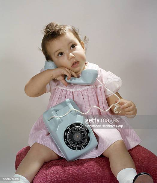 Toddler girl with curls in her hair listening on light blue dial telephone wearing a pink dress sitting on a red stool Syosset New York 1955