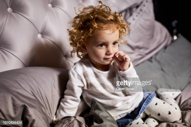Toddler girl with curly hair sitting in bed