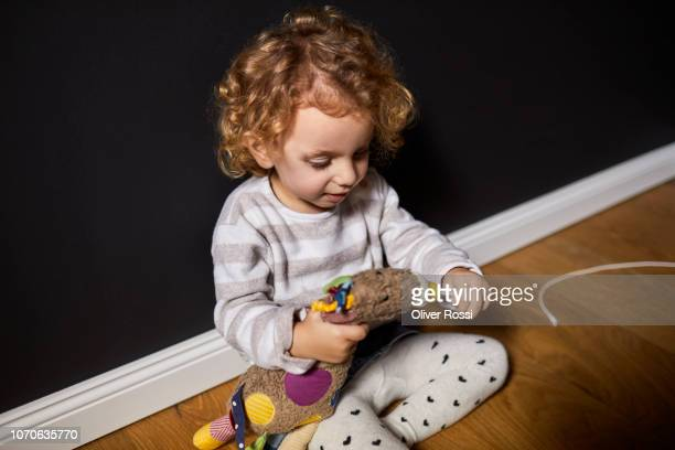 Toddler girl with curly hair sitting on bed with cuddly toy