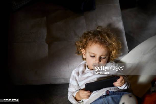Toddler girl with curly hair using cell phone