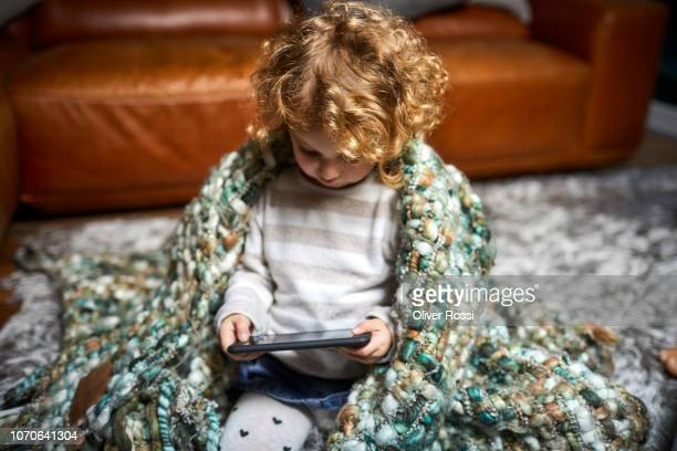 Toddler girl with curly hair wrapped in a blanket using cell phone