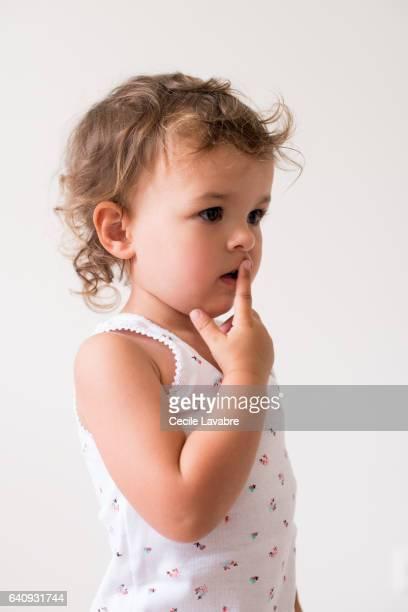 Toddler girl with finger on lips