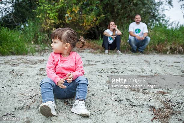 Toddler girl with parents in background