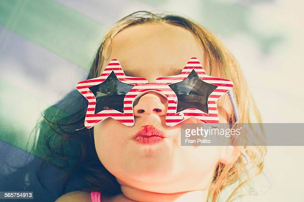 Toddler girl with patriotic sunglasses.