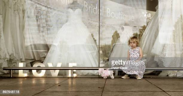 Toddler girl with toy dog sat outside bridal shop window