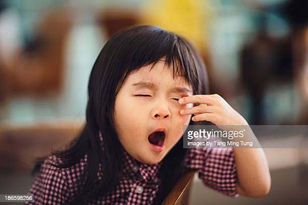 toddler girl yawning & rubbing eyes in cafe - あくび ストックフォトと画像