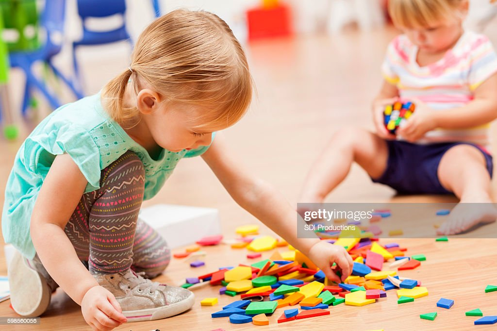 Toddler girls playing with puzzle pieces in a preschool classroom : Stock Photo