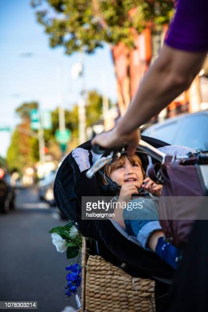 Toddler Grinning Up at Mother from Bike Basket
