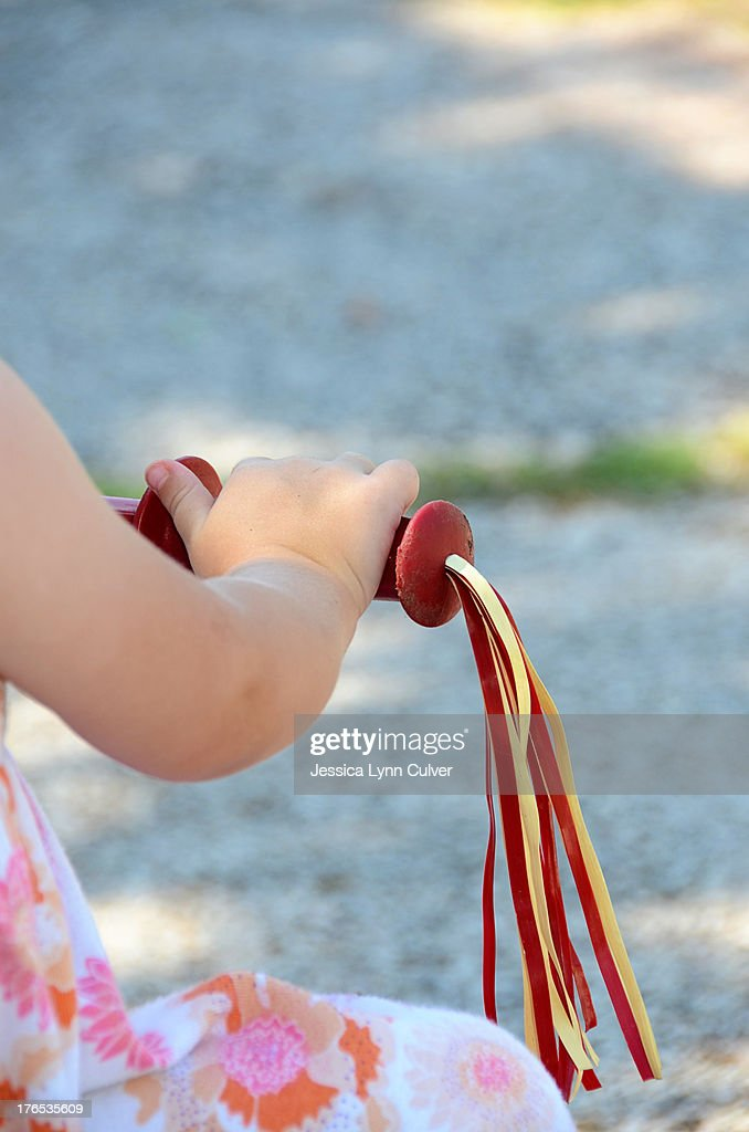Toddler hand on a tricycle : Stock Photo