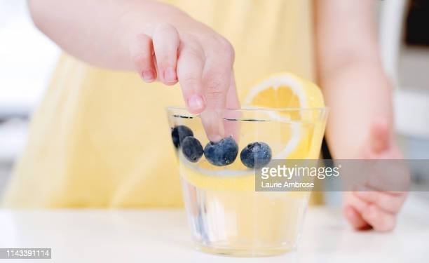toddler hand picking fruit out of water - infused water stock pictures, royalty-free photos & images