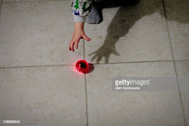 Toddler hand reaching for red bouncy ball