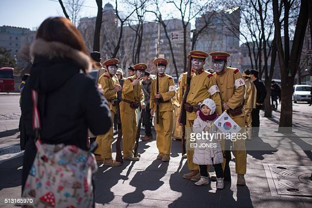 A toddler has her photo taken with activists dressed as colonialera Japanese soldiers prior to an antiJapan protest marking the 97th Independence...