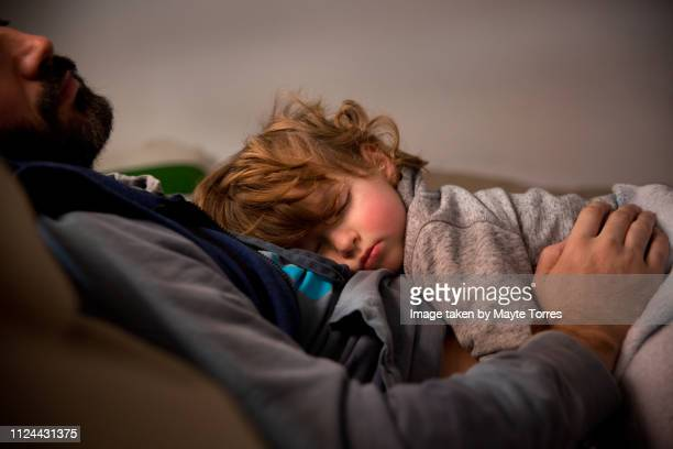 toddler having a nap with dad in the sofa - zakenman stock pictures, royalty-free photos & images