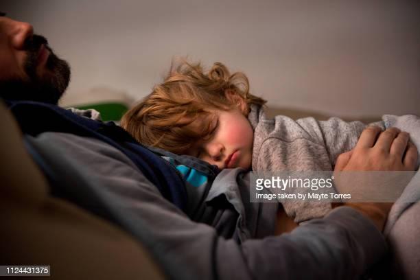toddler having a nap with dad in the sofa - sonnecchiare foto e immagini stock