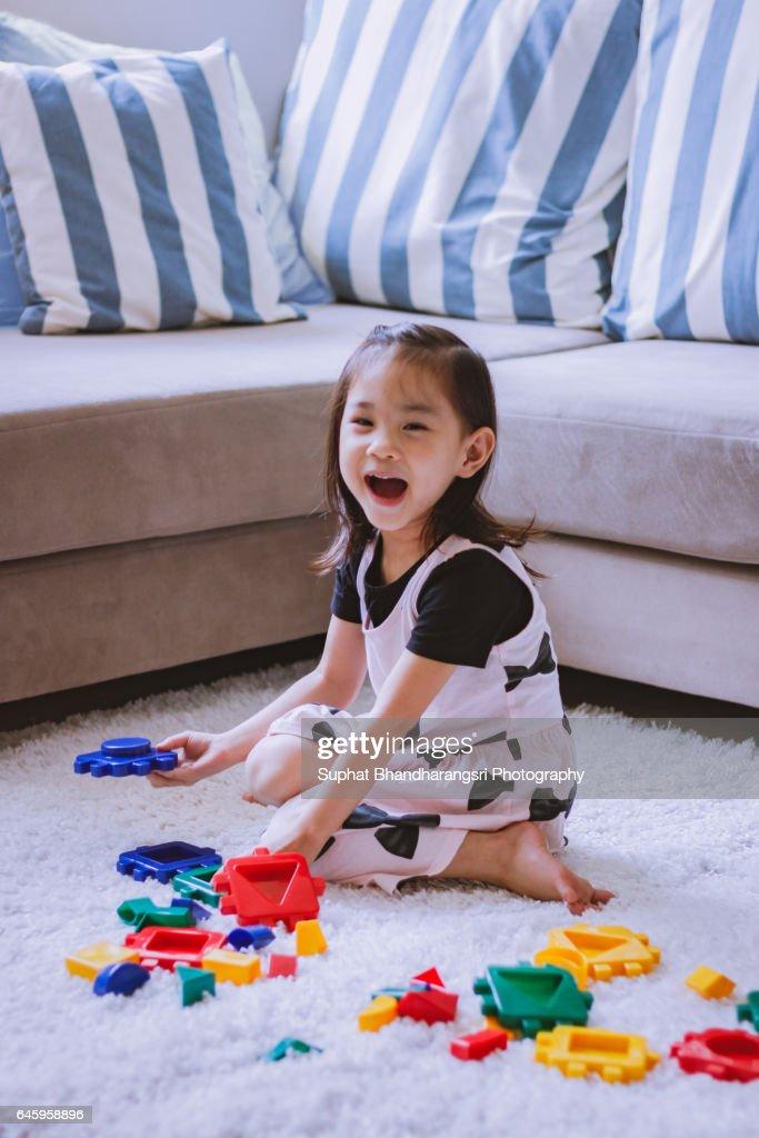 Toddler having fun building toy blocks : Stock Photo