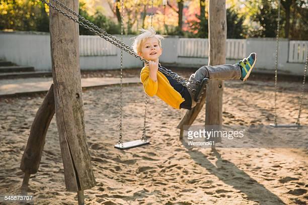 toddler having fun on a swing - kinderspielplatz stock-fotos und bilder