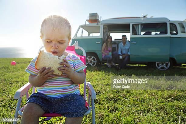 Toddler having sandwich with family in camper van