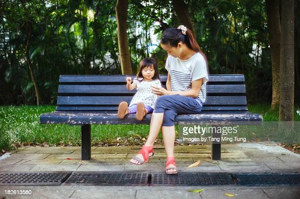 Toddler having yoghourt on bench with young mom