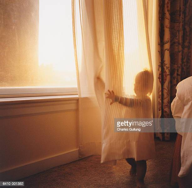 Toddler Hiding behind Curtain