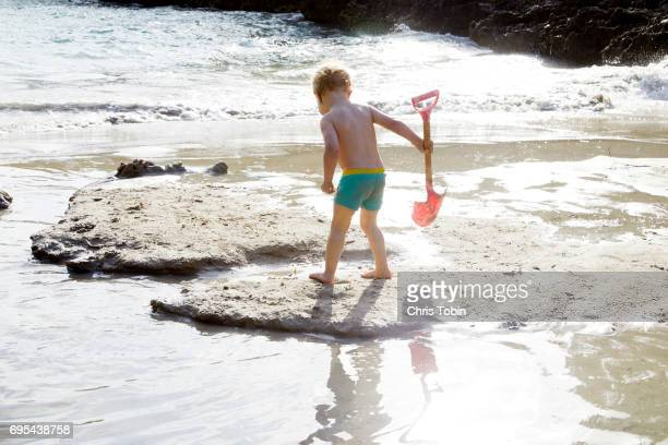 Toddler holding a shovel while standing on the beach surrounded by water