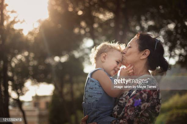 toddler holding grandma's face while she kisses him - alertness stock pictures, royalty-free photos & images