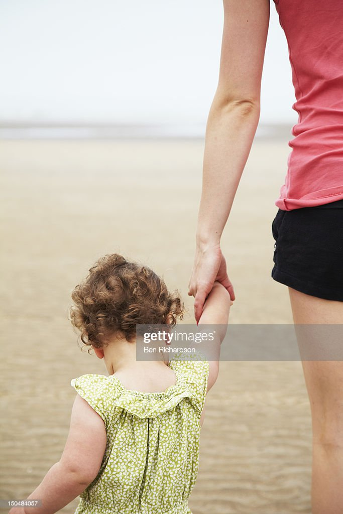Toddler holding hands on beach : Stock Photo
