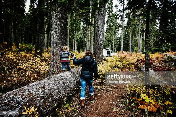 Toddler holding mothers hand and walking on log