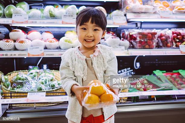 Toddler holding packed fruit smiling at camera