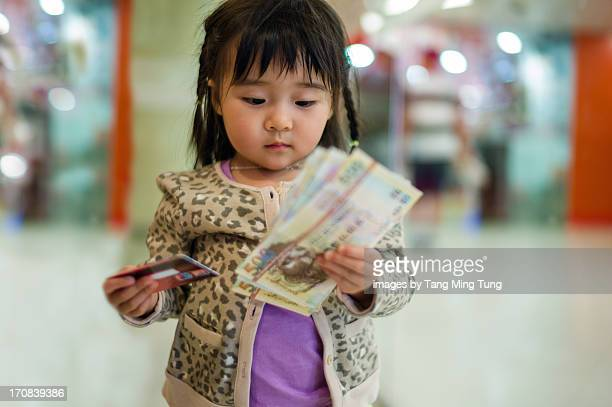 Toddler holding stack of banknotes & credit card