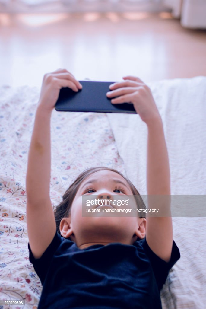Toddler holding up smartphone to watch her favorite cartoon : Stock Photo