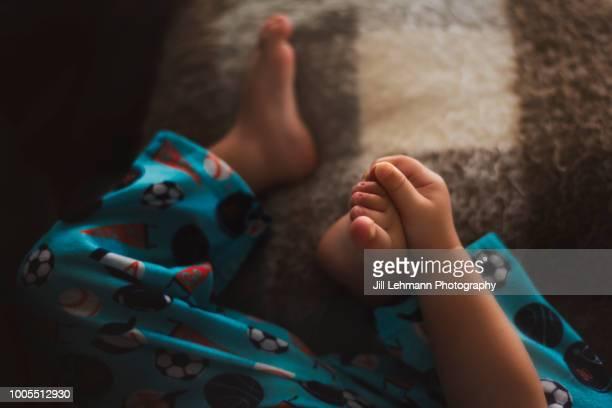 toddler holds foot and toes after hand, foot, and mouth disease - huidaandoening stockfoto's en -beelden