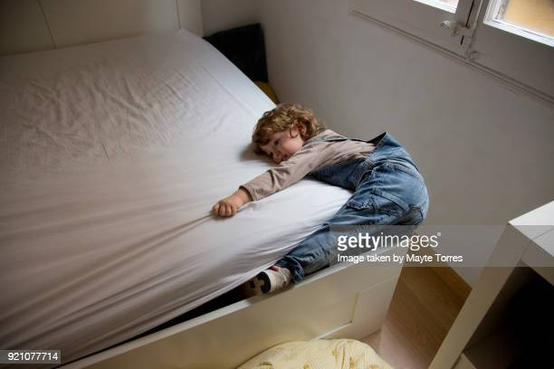 toddler hugging mattress - child in bed clothed stock pictures, royalty-free photos & images