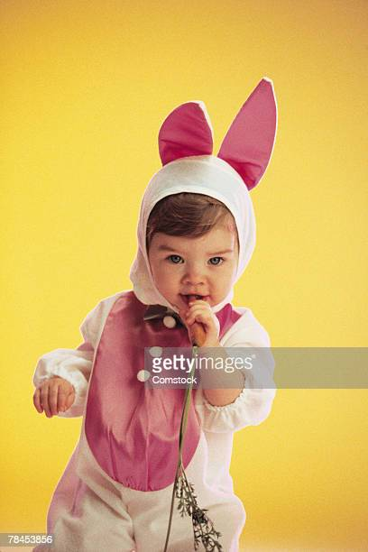 Toddler in a bunny costume holding a carrot