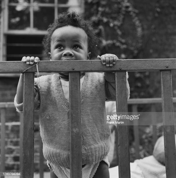 Toddler in a cot at a day nursery in the Notting Hill area of west London, circa 1958.