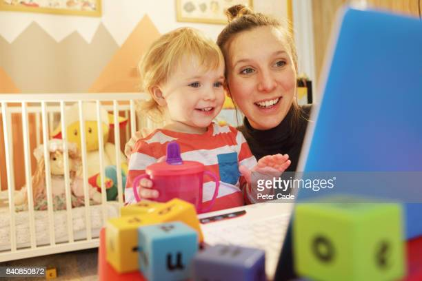 Toddler in bedroom looking at on laptop with mother