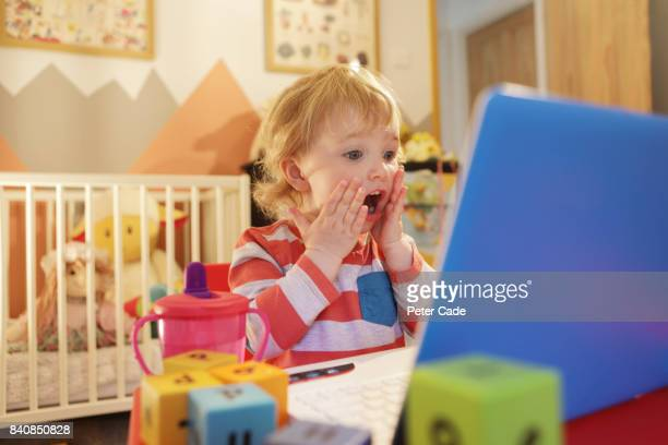 toddler in bedroom working on laptop, looking worried - mistake stock pictures, royalty-free photos & images