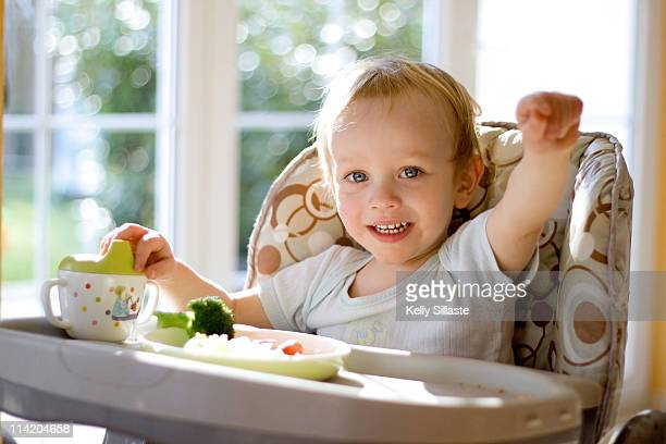 Toddler in highchair eating lunch