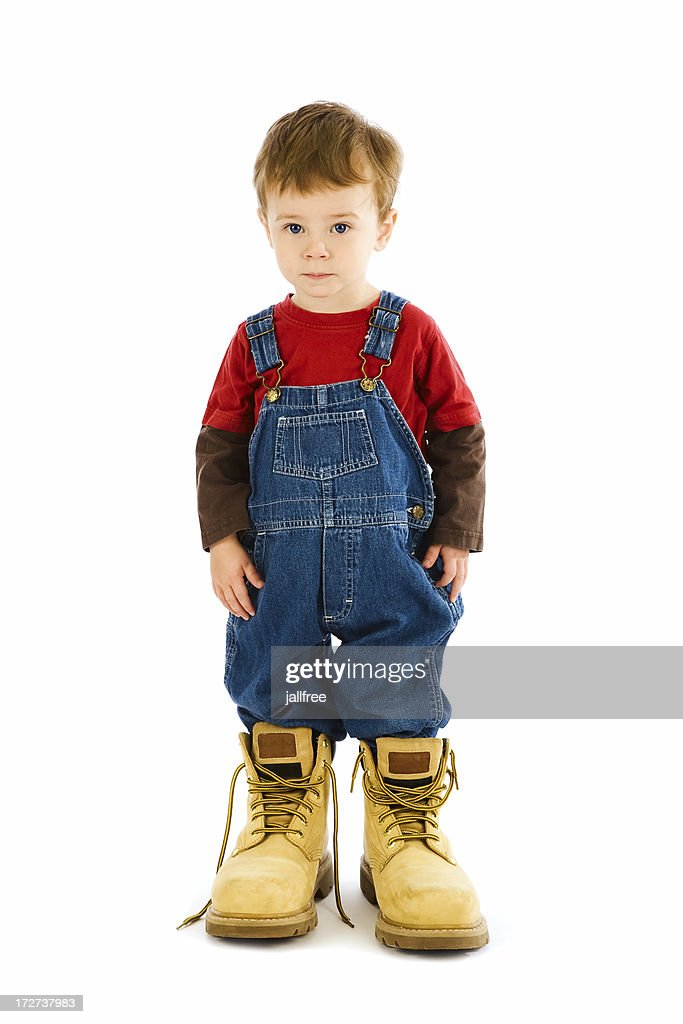 Toddler in oversize boots on white background : Stock Photo