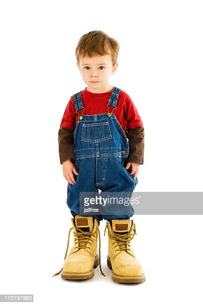 Toddler in oversize boots on white background