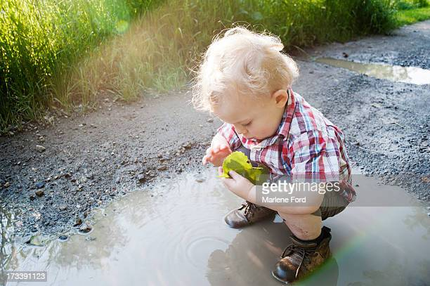 Toddler in puddle looking at a leaf