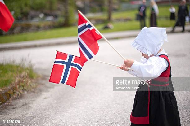 Toddler in traditional dress with norwegian flags