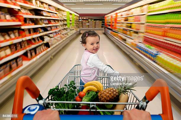 toddler in trolley in supermarket motion blur - supermarket stock pictures, royalty-free photos & images